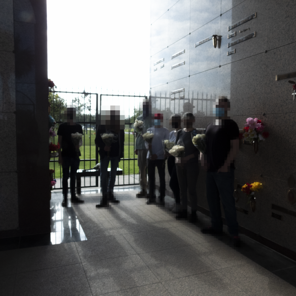 People standing with flowers inside the Mausoleum where George Floyd is buried.